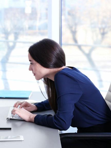 ragazza seduta alla scrivania con una postura scorretta
